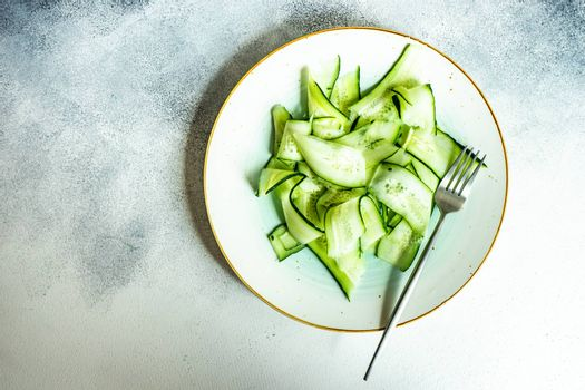 Organic vegetable salad with cucumber slices served on white background