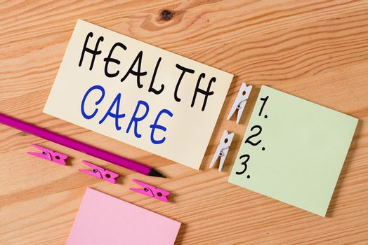Writing note showing Health Care. Business photo showcasing organized provision of medical care to individuals or community Colored clothespin papers empty reminder wooden floor background office.