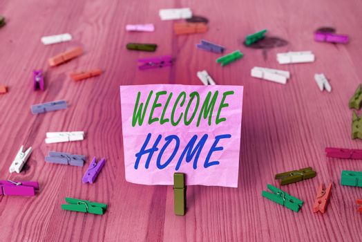 Text sign showing Welcome Home. Conceptual photo Expression Greetings New Owners Domicile Doormat Entry Colored crumpled rectangle shaped reminder paper light blue background.