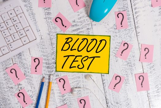 Text sign showing Blood Test. Conceptual photo Extracted blood sample from an organism to perfom a laboratory analysis Writing tools, computer stuff and scribbled paper on top of wooden table.