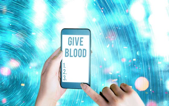 Handwriting text writing Give Blood. Concept meaning an individual voluntarily has blood drawn and used for transfusions Modern gadgets with white display screen under colorful bokeh background.