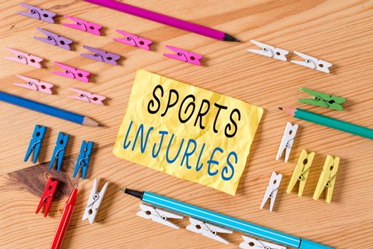 Text sign showing Sports Injuries. Conceptual photo injuries that occur when engaging in sports or exercise Colored clothespin papers empty reminder wooden floor background office.
