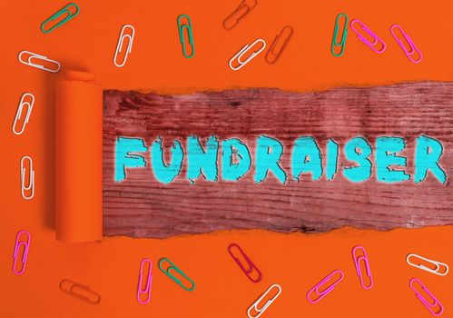 Writing note showing Fundraiser. Business photo showcasing an individual whose job or task is seek financial support for charity Rolled ripped torn cardboard above a wooden classic table.