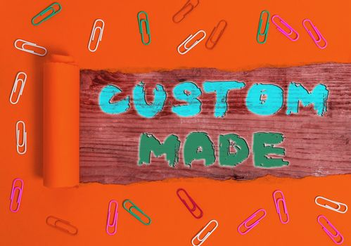 Writing note showing Custom Made. Business photo showcasing something is done to order for particular customer organization Rolled ripped torn cardboard above a wooden classic table.