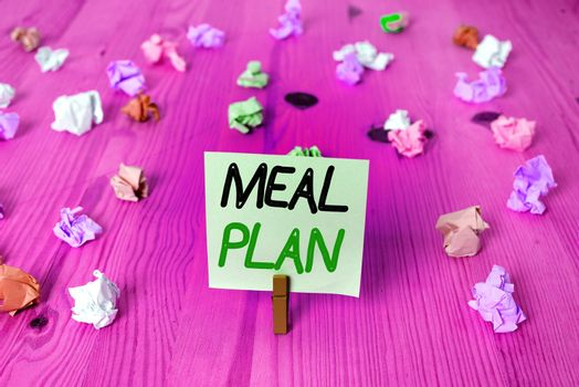 Word writing text Meal Plan. Business concept for act of taking time to plan any number of meals for the week Colored crumpled rectangle shaped reminder paper light blue background.