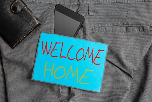 Handwriting text writing Welcome Home. Concept meaning Expression Greetings New Owners Domicile Doormat Entry Smartphone device inside trousers front pocket with wallet and note paper.