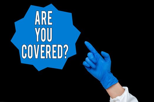 Conceptual hand writing showing Are You Covered Question. Business photo text asking if they had insurance in work or life Empty sticker paper accessories smartphone with medical gloves on.