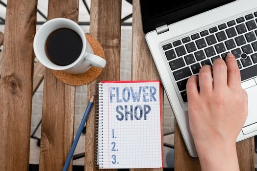 Conceptual hand writing showing Flower Shop. Business photo showcasing where cut flowers are sold with decorations for gifts Workplace overview with laptop used for individual interest.