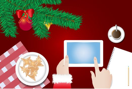 Finger of Santa Claus is touching a blank screen of tablet ready for your text over the table with  branch of Christmas tree, Christmas sweets on the plate and  cup of coffee.