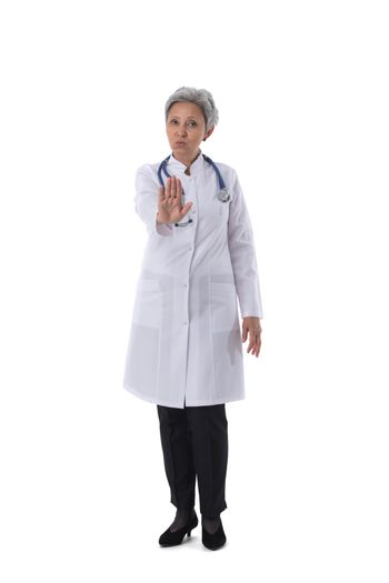 Asian mature female medical doctor with stethoscope showing stop gesture isolated on white background