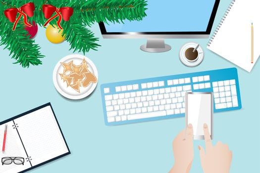 Top view of the office desk with twig of Christmas tree, blank notebook, paper with pen, PC monitor and keyboard. Hands are holding a smart phone and finger is touching a blank screen.