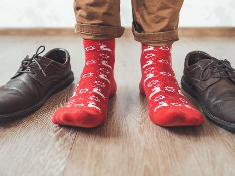Young man in chinos trousers and bright red socks with reindeers on them is ready to wear sude shoes. Scandinavian pattern. Winter holiday spirit. Casual outfit for New Year and Christmas celebration.