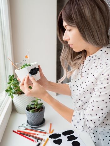 Smiling woman shows handmade decorations for Halloween. DIY flags and Boo! sticker on flowerpot with succulent plant. Socially-Distanced Halloween at home.