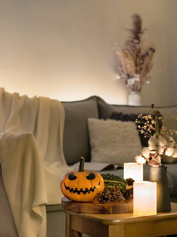Cozy scandinavian style halloween interior. Bright orange pumpkin with Jack-o-lantern laughing face, candles on sofa background. Vertical. Copy space.