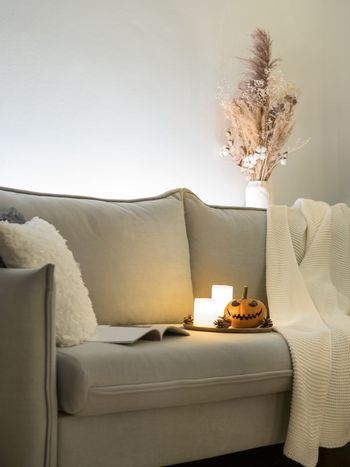 Cozy scandinavian style halloween interior. Bright orange pumpkin with Jack-o-lantern laughing face, candles on sofa. Vertical. Copy space.