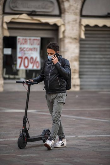 terni,italy october 26 2020:boy with medical mask causes covid 19 and carries the scooter