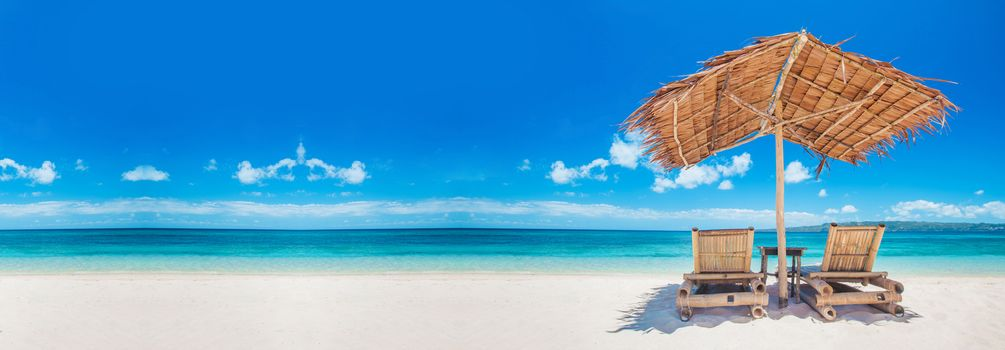 Beach chairs and umbrella on a beautiful tropical sea beach, view with copy space