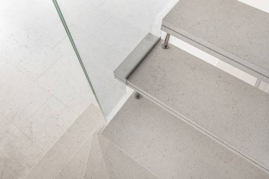 Grey microcement stairs with glass handrail. Stairs viewed from above. Modern design and innovative material. Glass railing.