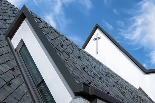 Particular roof of an Italian Catholic church. Church roof with angelic blue sky