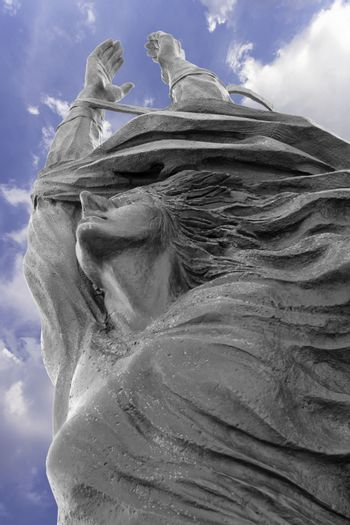 Statue of a woman with arms outstretched upwards. Peace, freedom, Easter concept and more.