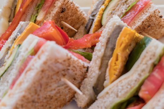Vegetarian sandwiches. Healthy toasts with omelette, peppers, courgettes and tomatoes for breakfast or lunch. Plant-based diet. Whole food concept. Close-up.