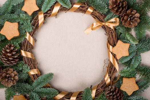 Christmas decorative wreath with noble fir tree twigs pine cones and gingerbread cookies on craft paper background with copy space for text