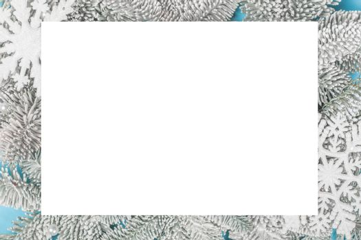 Frosted fir tree twigs and Christmas decorative snowflakes on blue background with white rectangle card with copy space for text template flat lay top view design