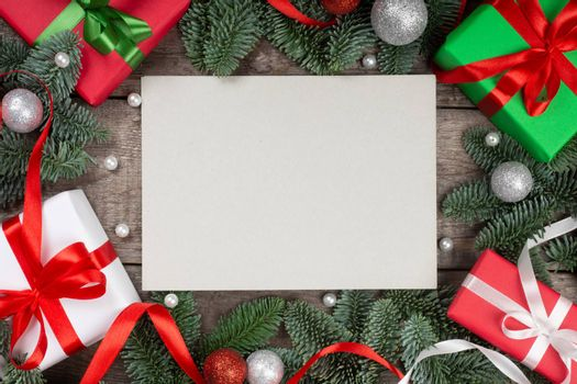 Christmas or New Year background composition made of Xmas decorations and fir tree branches and gifts with copy space for text on card