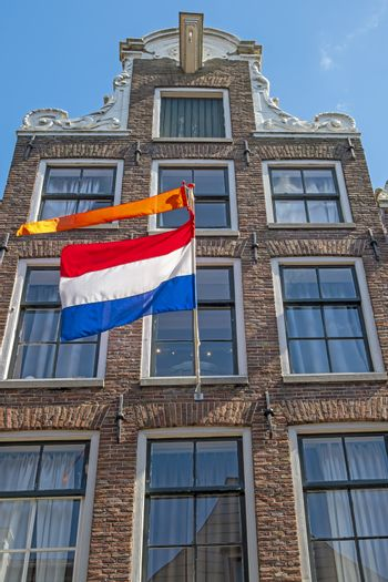 Old medieval townhouse with the national dutch flag and orange b