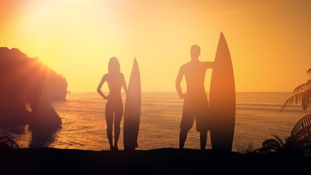 Couple of surfers lit by the setting sun.