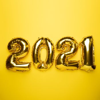 2021 concept new year from golden foil balloon on yellow stock photo