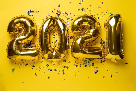 2021 numbers for new year from golden foil balloon and confetti stock photo
