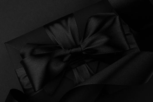 Black friday gift, paper box with silk ribbon bow on black paper background with copy space for text, flat lay top view template