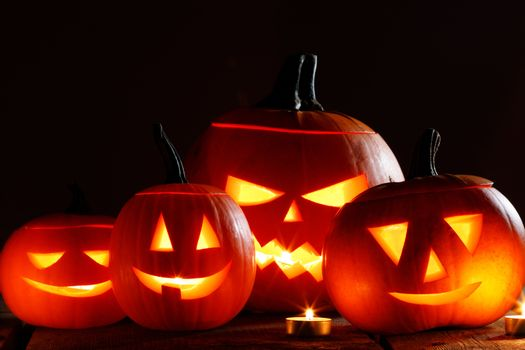Halloween pumpkin head lanterns and burning candles on wooden background isolated on black