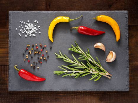 Herbs and spices on slate background. Top view or flat lay. Food background and food ingredients - rosemary, hot peppers, garlic bulbs. casher salt and peppercorns