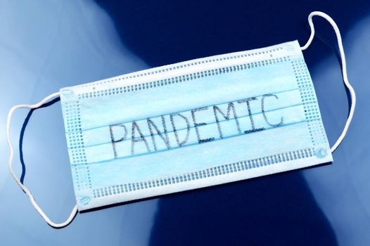 A face mask with the handwritten word Pandemic for the global Coronavirus outbreak starting in 2019.