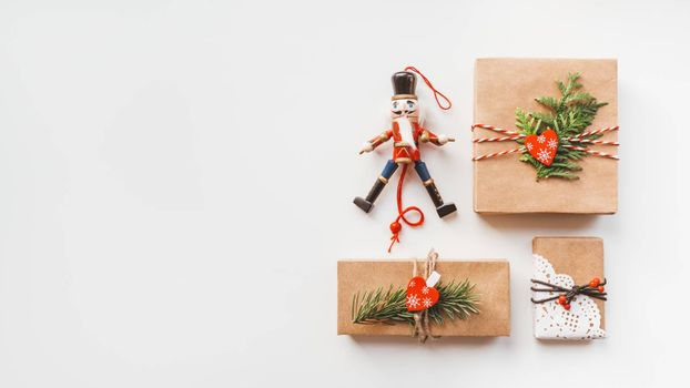 Christmas DIY presents wrapped in craft paper and wooden Nutcracker toy. Decorations on New Year gifts. Festive background. Winter holiday spirit. White background with copy space.