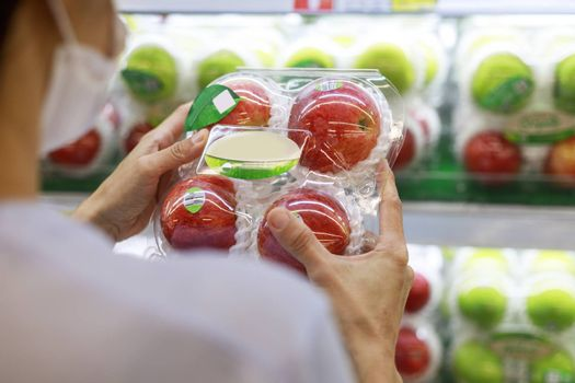 Women long hair wear protective face mask hands holding green apples ipackage. Asian female shopping at supermarket, Grocery to buy some food. New normal after covid-19 concept.