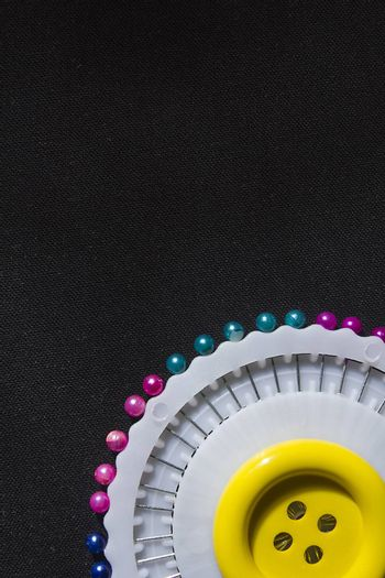 Set of colorful safety pins on black fabric background