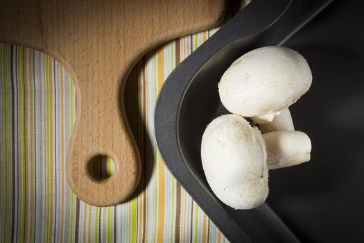 Champignon mushrooms on a baking sheet and a cutting board on the kitchen table