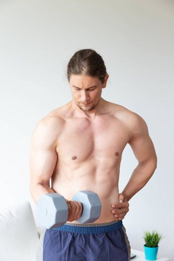 Athletic young man doing exercise with dumbbell in living room at home