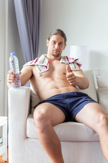 a sport man sit and relax with a bottle of drink water in living room at home