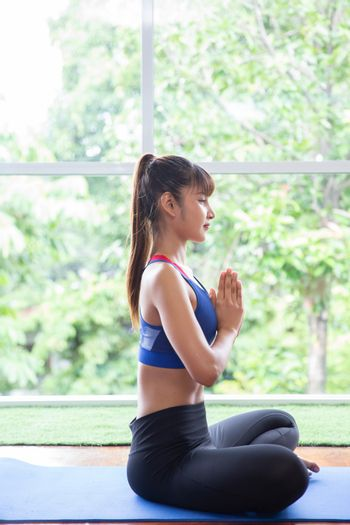 A sport girl relax exercise yoga in lotus position at home