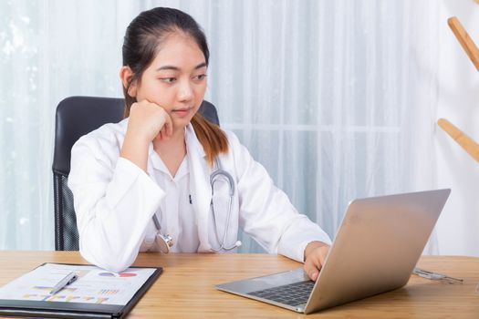 female doctor sit on her desk in the office focus on her job on laptop and smile