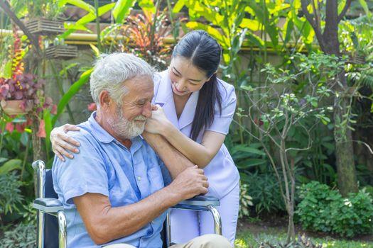 A nurse take care a senior male on wheelchair in his garden at home