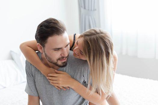 Caucasion couple hug on bed in bedroom