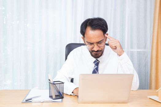 Businessman thinking and focus on this work seriously with his computer notebook in the office