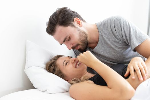 Caucasion couple feeling happy on bed in bedroom