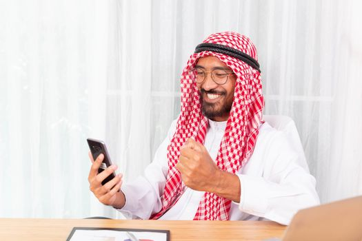 Arabian businessman smile and happy reading a good news from his mobile phone in his office