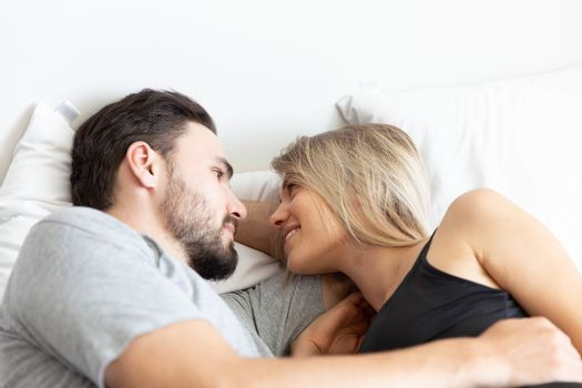 Young cute couple hug and sleep together in bed